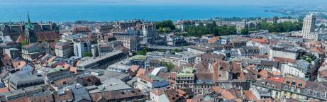 Vue sur les toits des maisons de la ville de Lausanne avec le lac en fond d'image.