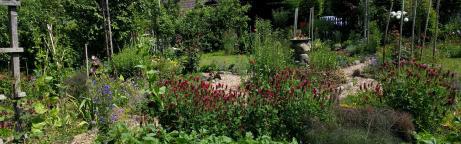 Naturnaher Nutz- und Blumengarten mit blügenden Blumen und Gemüsebeeten