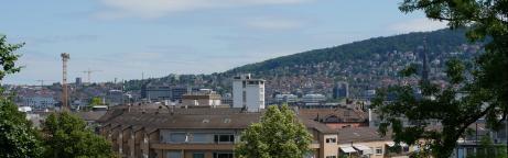 Blick auf Zürich: Bäume im Vordergrund mit Häusern