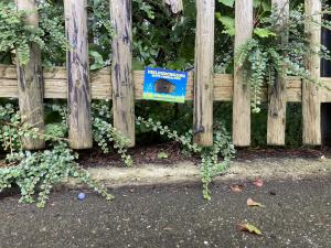 Die Lücke eines Holzzaunes wurde als Igeldurchgang mit einer Plakette markiert
