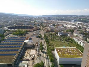 Ausblick über die Hardau mit Blick auf ein Dach mit Solarpanels, ein begrüntes Dach und viele unbegrünte Dächer.