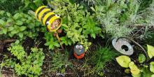 Gebastelte Insekten mit grünen Pflanzen im Hintergrund